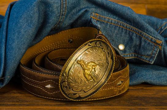 Vintage Western Belt Buckle on Rustic Wood with Denim Shirt