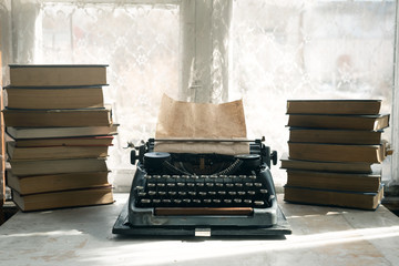 Typewriter and stack of books on a writer table background.