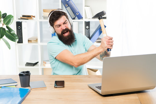 Outdated software. Computer lag. Reasons for computer lagging. How fix slow lagging system. Hate office routine. Man bearded guy headphones office swing hammer on computer. Slow internet connection