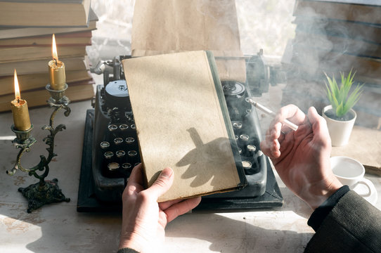 A writer is holding in hands a closed book with copy space and is smoking a cigarette by sitting his table.