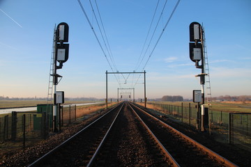 Railroad double track in Moordrecht during sunrise with signals in the low polder heading from Rotterdam to Gouda
