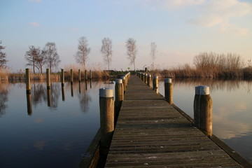Pier at the Rottemeren colored by the sunlight during sunset in Zevenhuizen