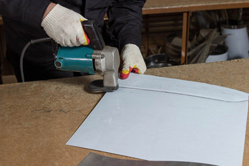 Sheet Metal Cutting Electric Shears. Cutting of metal sheets with industrial hand-operated scissors.