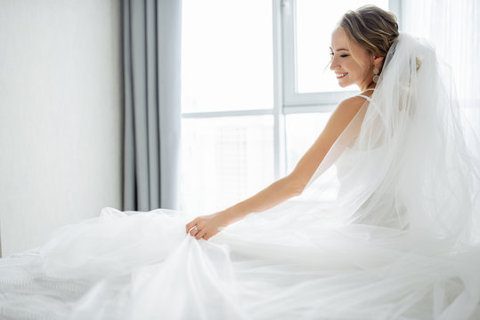 Amazing young bride posing in a beautiful wedding dress with wedding veil near window and smiling