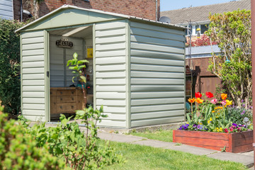 A modern shed and breautiful grden with blooming flowers and a Dads hideout sign in the shed.