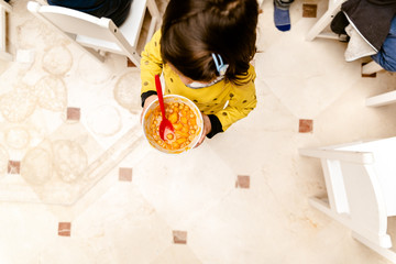 Girl walking with a bowl of stew in the dining room of her nursery school, top view, with copy space.
