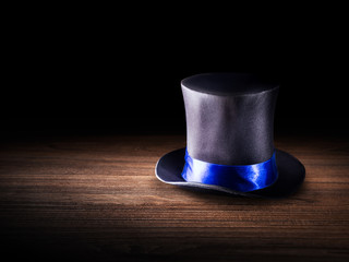Wall Mural - high contrast image of a magician hat on a wooden background