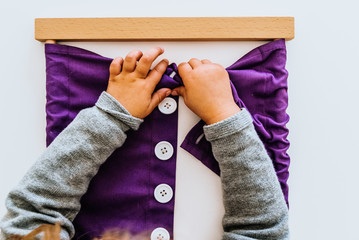 Hand of a student handling montessori material inside a classroom.