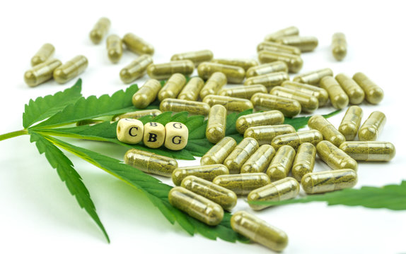 Group of clear CBG Cannabigerol capsules and hemp leaf isolated on white