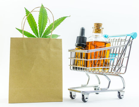 Supermarket trolley with marijuana leafs and medical cannabis oil cbd, isolated on white