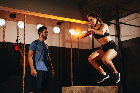 Fit young woman doing a box jump exercise. Sports woman doing a box squat at the gym