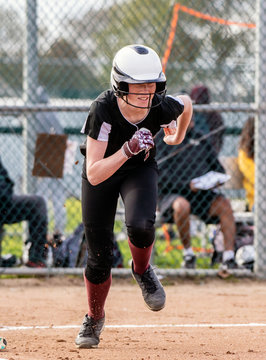 Female softball base runner smiling through her face mask while sprinting to first base.