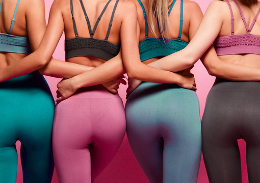 Group of four women buttocks in blue gray and brown sport wear standing together after workout on pink