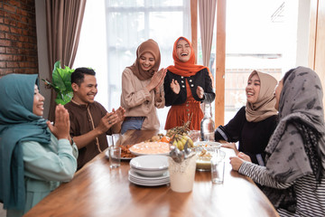 muslim friend and family laughing together while having lunch together at home