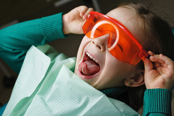 Little girl sits in dental chair and wears protective glasses. She dabbles.