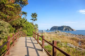 Fototapete - Footpath along the sea on the island of Jeju South Korea beautiful seascape. View of the lighthouse. Travel to Asia