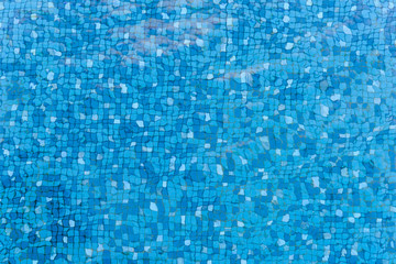 Top view of water ripples on blue mosaic tiled. bottom of swimming pool. background