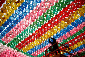 A worker attaches prayer petitions, with names written on cards, to lotus lanterns in preparation for the upcoming birthday of Buddha, at Jogye temple in Seoul