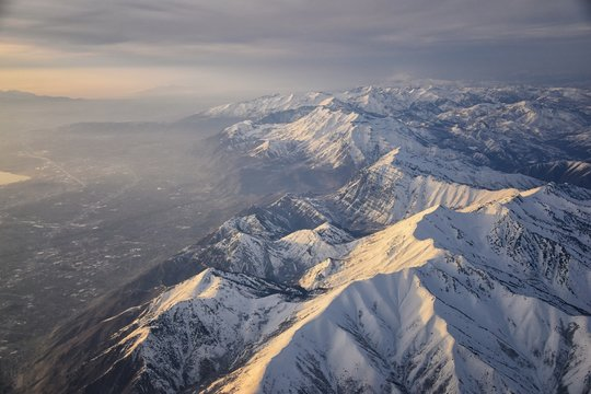 Aerial view from airplane of the Wasatch Front Rocky Mountain Range with snow capped peaks in winter including urban cities of Provo, Farmington Bountiful, Orem and Salt Lake City. Utah. United States