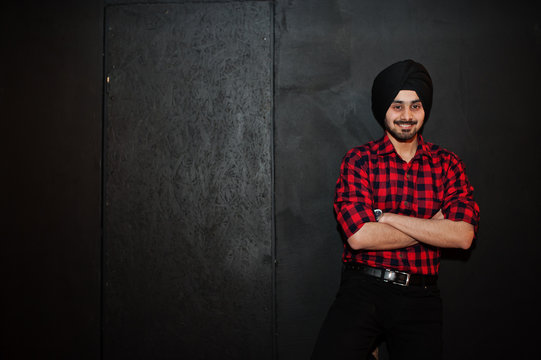 Indian man in checkered shirt and black turban against dark background.