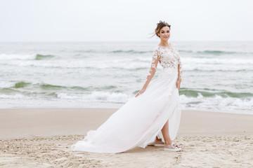 positive bride runs on the sea beach on an overcast day