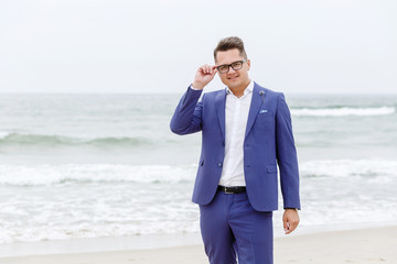 portrait of the groom in a blue suit and glasses on the sea beach