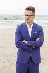 portrait of stylish groom in blue suit on the beach