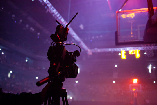 professional camera filming basketball game live in sports arena