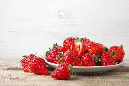 Fresh strawberries in plate on wood