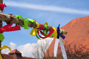 colorful ribbons at a cross of spruce trunks