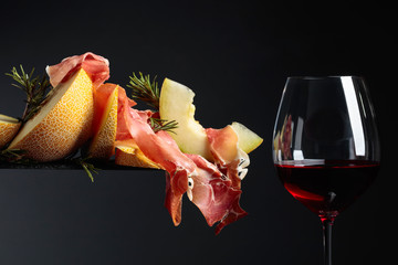 Red wine with prosciutto and melon.