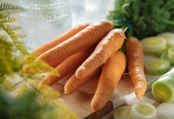 Branch of carrots on wooden and marble board