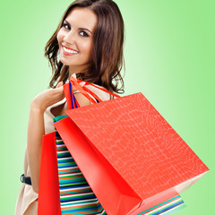Young happy woman with shopping bags, over green