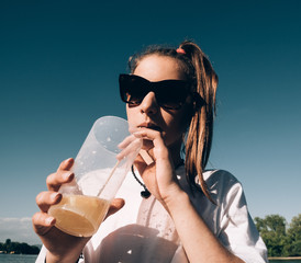 young girl drinking beverages outdoor with drinking  straw
