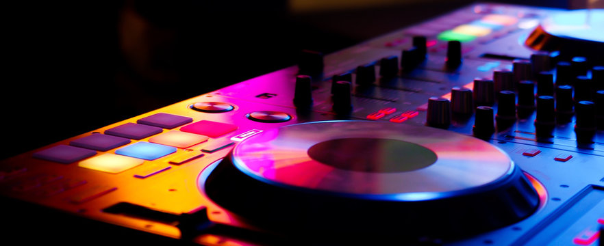 DJ controller colorful buttons live show at night club playing edm dance music in neon light