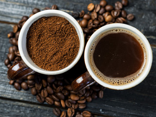 Whole roasted coffee, freshly ground coffee and brewed fragrant espresso in a Cup
