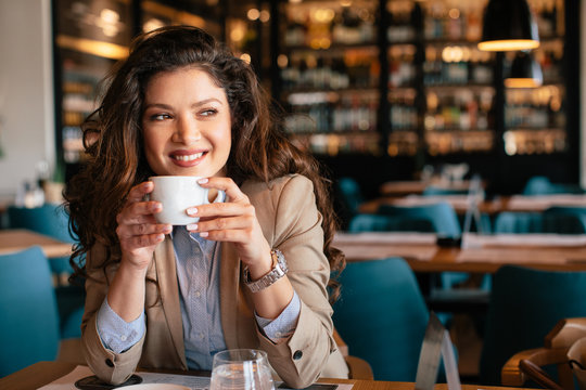 Young woman is drinking coffee in a cafe