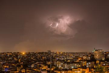 Fotomurales - Lightning storm over city in purple light