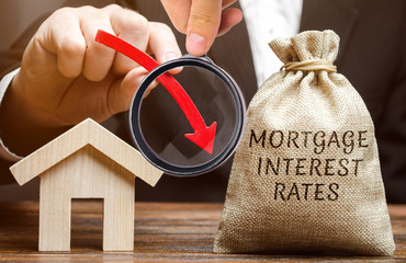 Bag with the money and the word Mortgage interest rates and arrow down and house. Low interest in mortgages. Reducing interest payments for mortgages. The fall in housing rates on credit. Analysis
