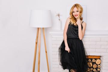 Beautiful blonde woman standing next to modern white floor lamp, nice white interior. Fashinable lady smiling, wearing elegant black dress. She has pretty wavy hair.