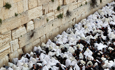 Jewish worshippers cover themselves in their prayer shawls as they pray during a priestly blessing on the Jewish holiday of Passover at the Western Wall, Judaism's holiest prayer site, in Jerusalem's Old City