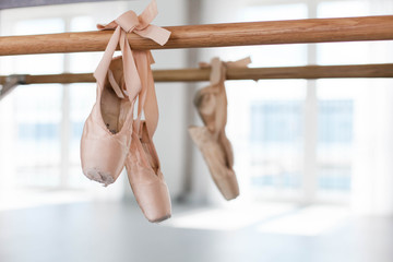 Old pointe shoes hang on ballet wooden barre in dance class room. Light sunny blurred background of ballet classic school. Reflection in mirror.