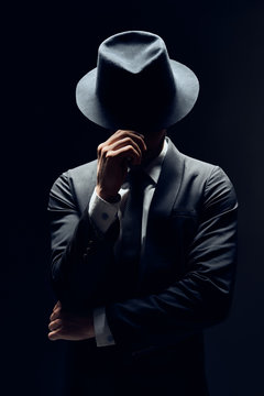 Man in suit hiding face behind his hat isolated on dark background