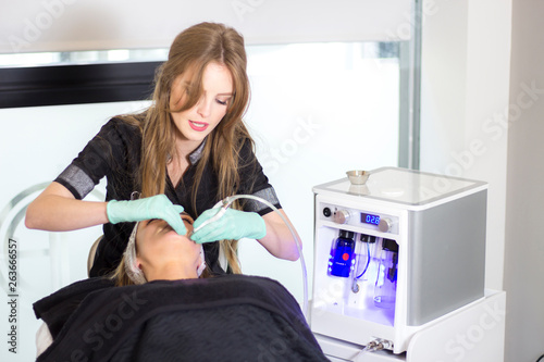 Attractive beautician applying ultrasound facial procedure with