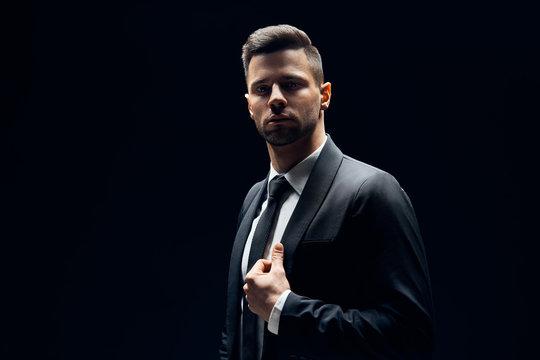 Handsome confident man in black suit on dark background