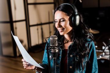 pretty woman in headphones singing in recording studio near microphone