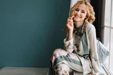 Beautiful young woman with long blonde wavy hair sitting on window sill in room with turquoise wall. She's smiling and enjoying morning time. Wearing nice pajama. Wall mural