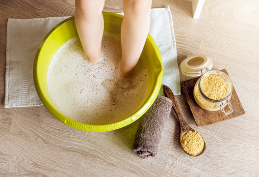 Child taking a healing warming foot bath with mustard powder, adding mustard powder to foot bath with wooden spoon. Against cold illness, aches and improves blood circulation. Alternative medicine.