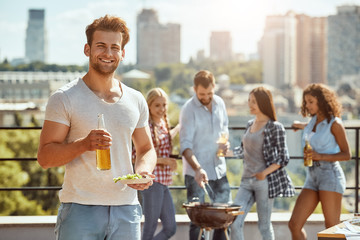 Enjoying barbecue with friends. Young and cheerful man is holding bottle of beer and plate of food while having a barbecue on the roof with friends.