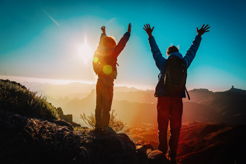 Father and son travel in sunset mountains, family hiking in nature